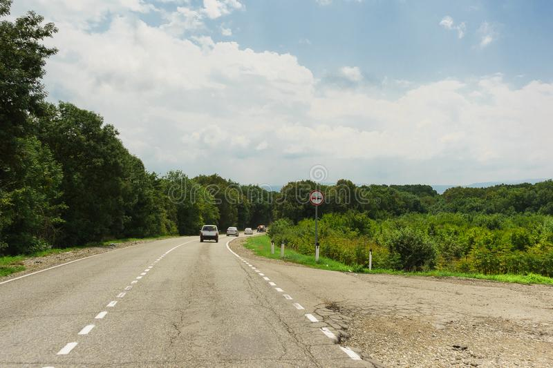 Turn on the old road in the Anapa district of the Krasnodar region. Road sign Overtaking is prohibited. Landscape in summer cloudy day stock photo