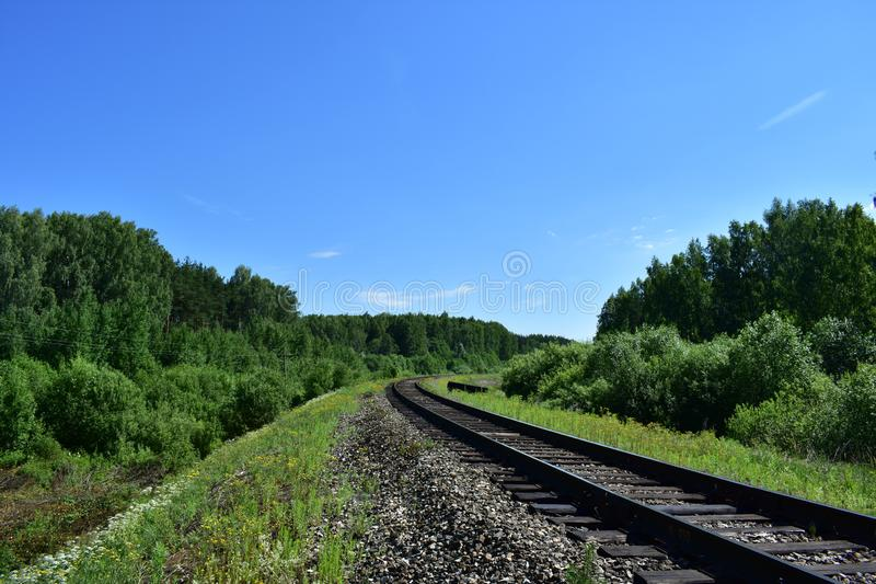 Turn the prospect of a distant railway dense forest and clear sky. The view is on the road and disappears in the distance, explore a variety of vegetation stock image