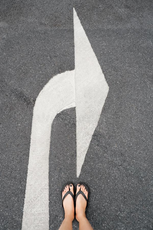 Turn Right Traffic Symbol. Feet and Arrows on Road Background. Woman Black Shoes or Sandals with Black Nail Polish Manicure Standi stock photography