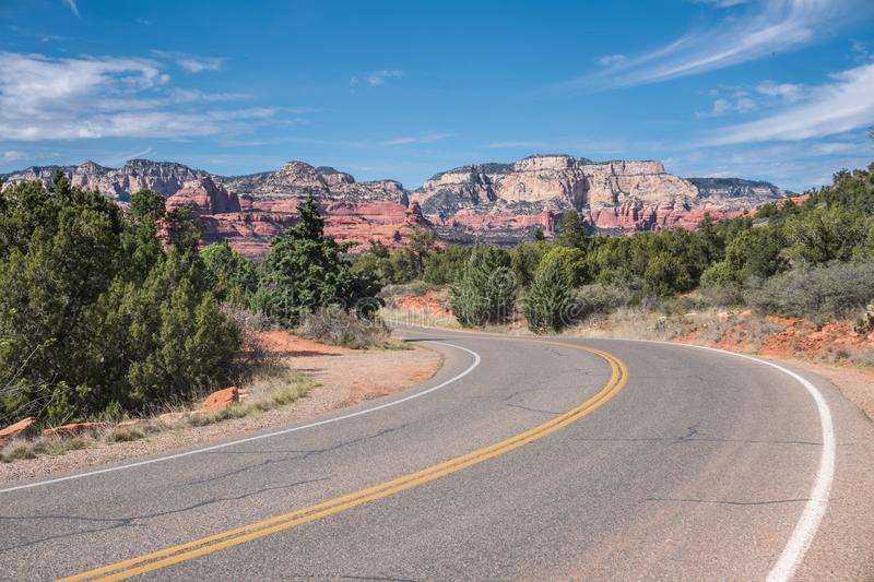 Turn on highway with view of Sedona red rock formations in Arizona, USA. Turn on two lane highway passing through red rock sandstone formations in Sedona royalty free stock photography