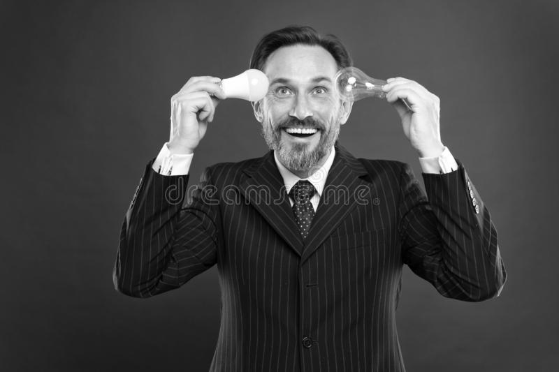 Turn your brains on. Power saving. Male in business outfit. Electricity and energy. Man with beard search for. Inspiration. Lamp. Businessman in suit hold light stock image