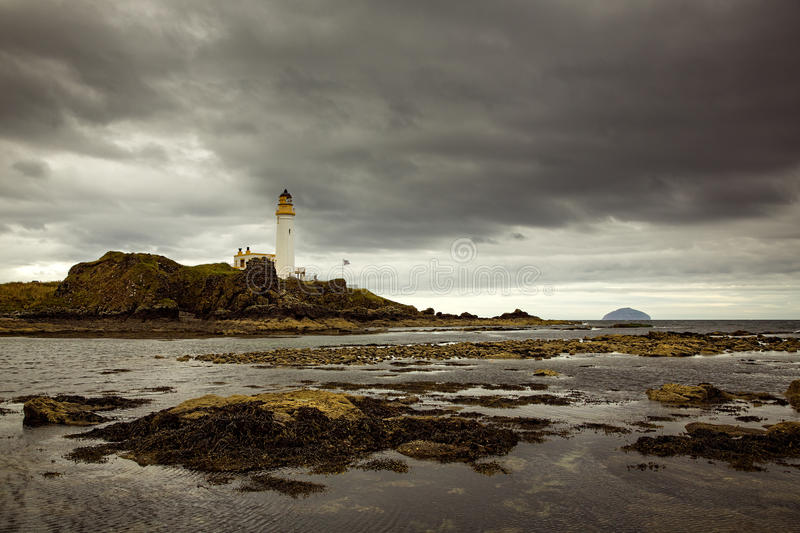 Turnberry Lighthouse in Scotland. Turnberry Lighthouse under grey clouds from the rocks offshore at low tide stock photos