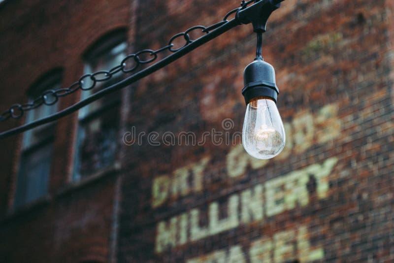 Turned on Black Lamp Near Brown Bricks Concrete Wall stock image