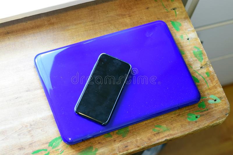 Turned off cell phone on top of closed laptop royalty free stock images