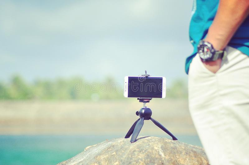 Turned Off White Android Smartphone With Mini Tri Stand on Rock royalty free stock images