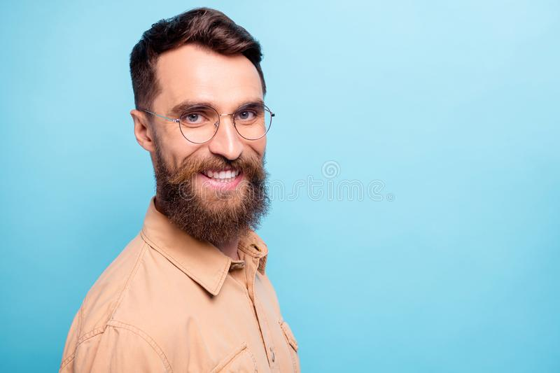 Turned photo of charming man looking with beaming smile wearing brown shirt  over blue background royalty free stock photos