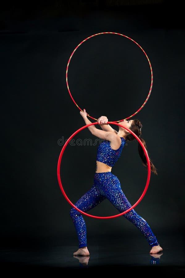 Turner die gymnastiekoefeningen met kleurrijke hoepel op een zwarte doen royalty-vrije stock afbeeldingen