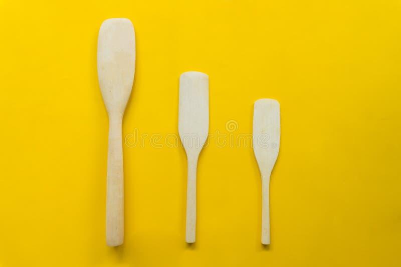 Turner en bois D'isolement faisant cuire la spatule avec le fond jaune images stock
