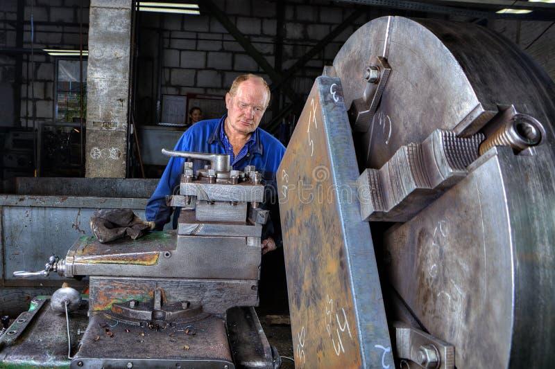Turner machine operator controls processing of metal big turning royalty free stock photos