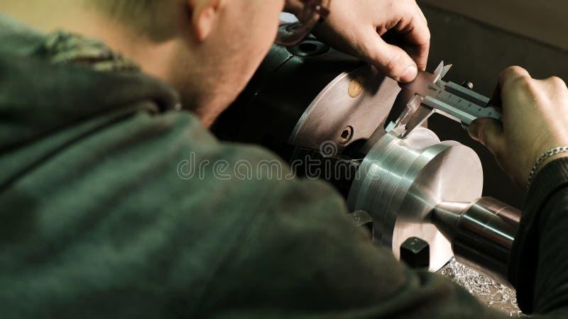 Turner misst die Maße des Metallwerkstückes mit einem Tasterzirkel Arbeit über eine Drehbank lizenzfreies stockfoto