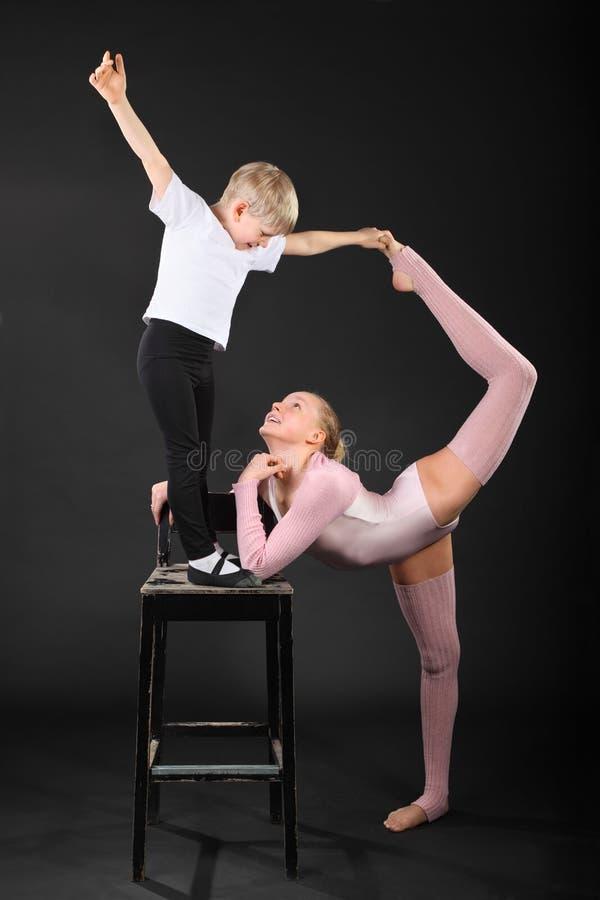 Turner van het meisje en van de jongen nam bevallig stelt bij stoel royalty-vrije stock fotografie