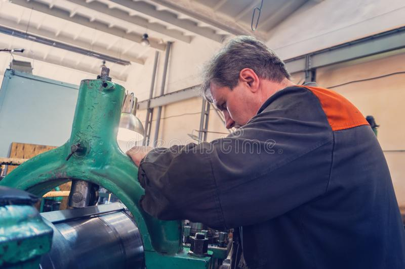 Turner worker manages the metalworking process of mechanical cutting on a lathe.  stock image