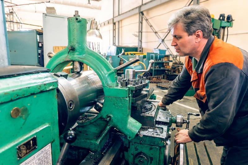 Turner worker manages the metalworking process of mechanical cutting on a lathe.  stock images