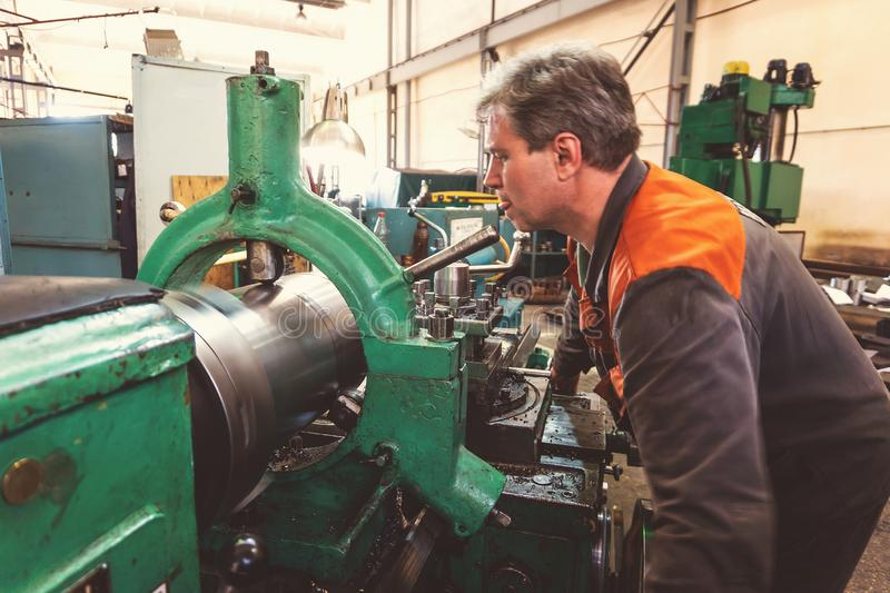 Turner worker manages the metalworking process of mechanical cutting on a lathe.  royalty free stock photos