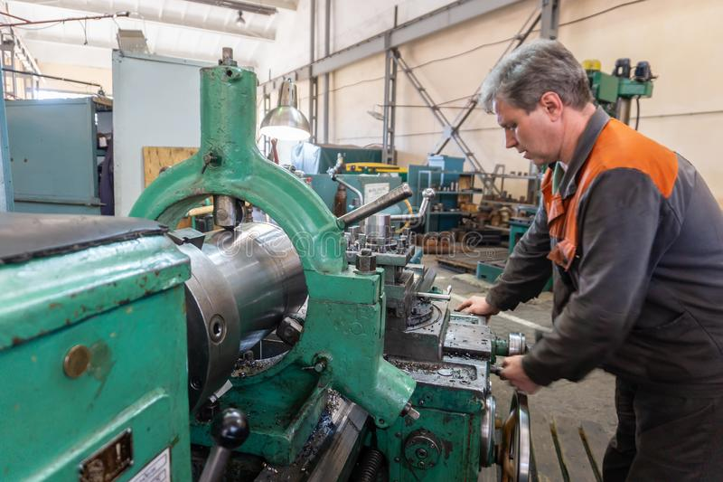 Turner worker manages the metalworking process of mechanical cutting on a lathe.  royalty free stock photo