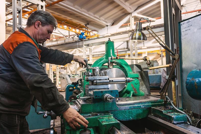 Turner worker manages the metalworking process of mechanical cutting on a lathe.  stock photography