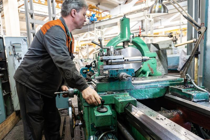 Turner worker manages the metalworking process of mechanical cutting on a lathe.  royalty free stock photography