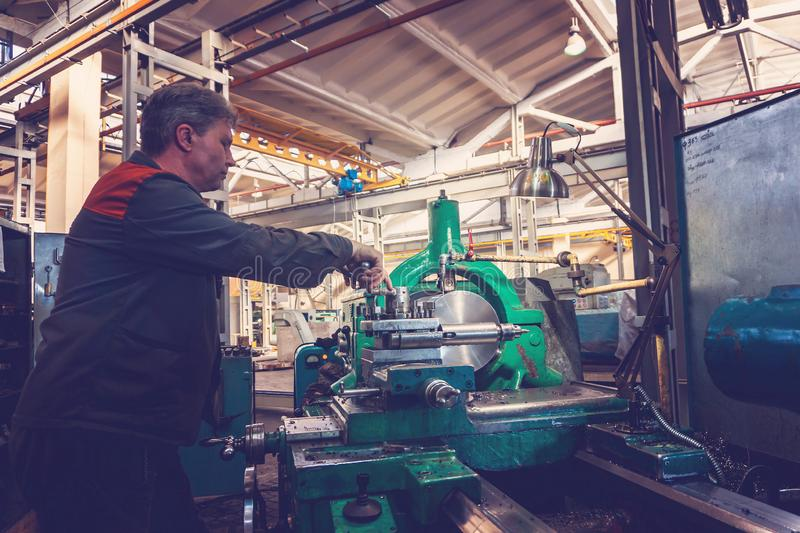 Turner worker manages the metalworking process of mechanical cutting on a lathe.  royalty free stock images