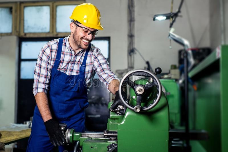 Turner worker is working on a lathe machine in a factory royalty free stock images