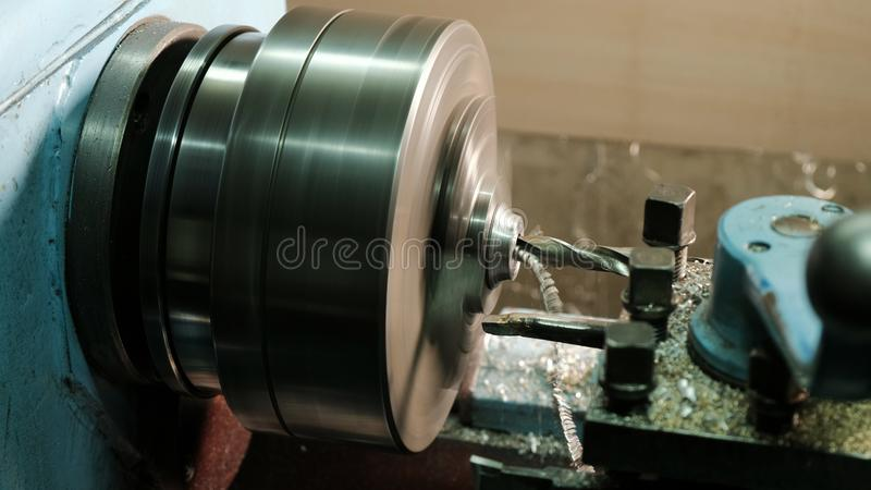 Turner is working on a turning lathe at the metal constructions factory. Heavy industry and metalwork. Accuracy metal. Cutting and detail drilling stock photos
