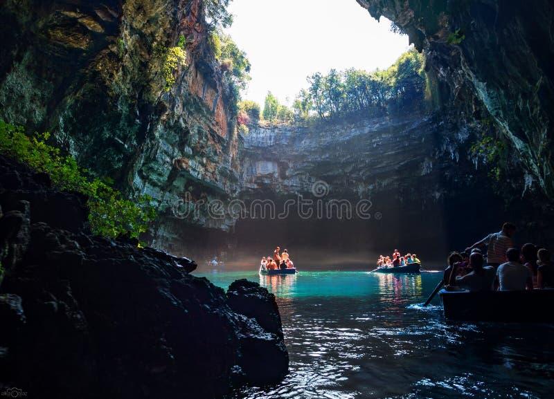 Turnera vid fartygturister i en grotta med en underjordisk sjö Melissani på ön av Kefalonia, Grekland royaltyfri foto