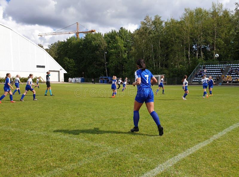Turnering för yngre fotboll för Helsingfors kopp - två kvinnliga lag som spelar en match arkivfoto