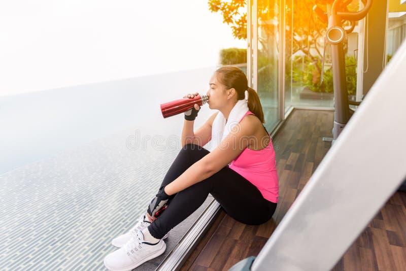 Turnhallenfrau, die sitzendes Trinkwasser in der Eignungsmitte ausarbeitet lizenzfreies stockfoto