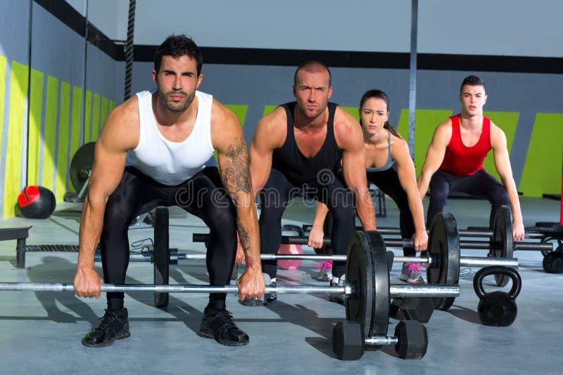Turnhallengruppe mit Gewichtsanhebenstange crossfit Training lizenzfreie stockfotos