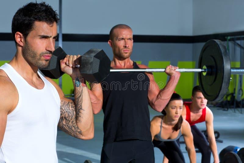 Turnhallengruppe mit Gewichtsanhebenstange crossfit Training stockfoto