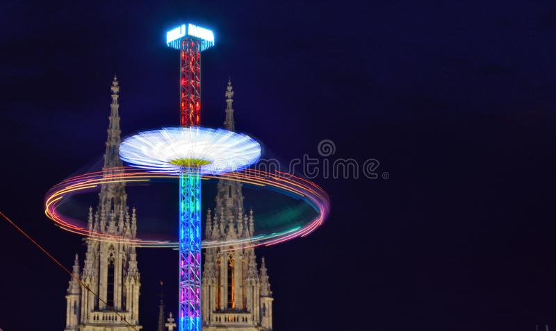 Turnig wheel of a fair attration and historic churchtowers. Turnig wheel of a fair attration and historic church towers at night in the city of Ostend, Belgium royalty free stock images