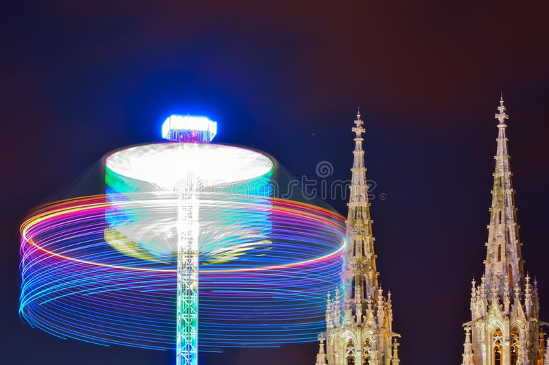 Turnig wheel of a fair attration and historic churchtowers. Turnig wheel of a fair attration and historic church towers at night in the city of Ostend, Belgium royalty free stock photography