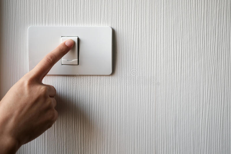 Turning on or off on light switch. Close up of finger is turning on or off on light switch. Copy space stock images