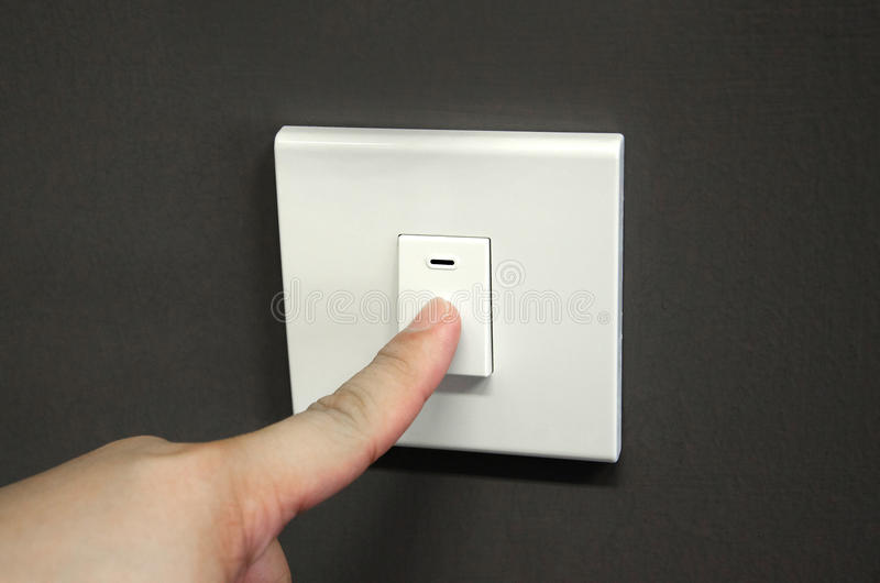 Turning off light switch. Close up finger turning off light switch on the wall stock photo