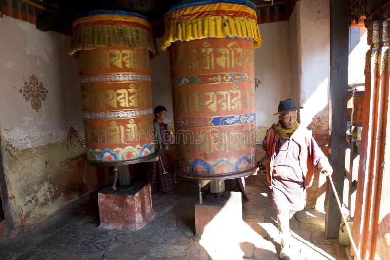 Turning prayer wheels, Jampey Lhakhang Dzong royalty free stock photo