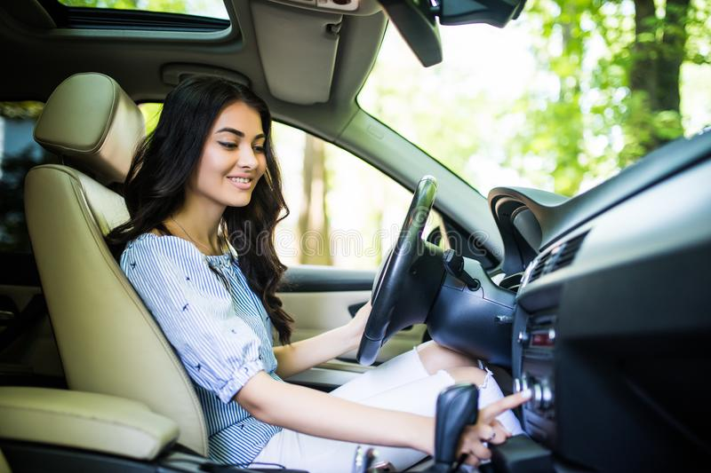 Young beauty woman change station on radio at car driving home. Turning on radio at car driving home stock photo
