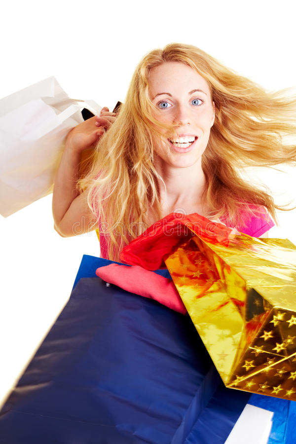 Turning and shopping. Happy woman with a lot of colorful shopping bags royalty free stock photos