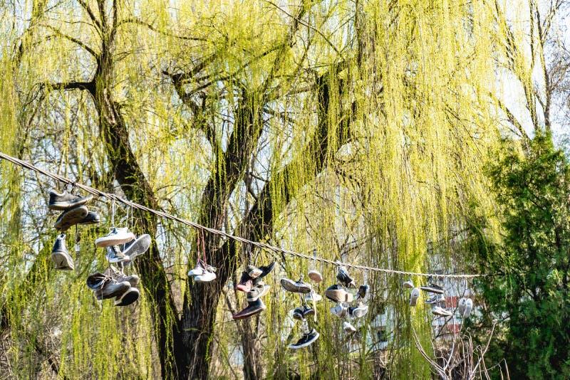 Turnschuhe, die an einem Draht hängen stockbilder