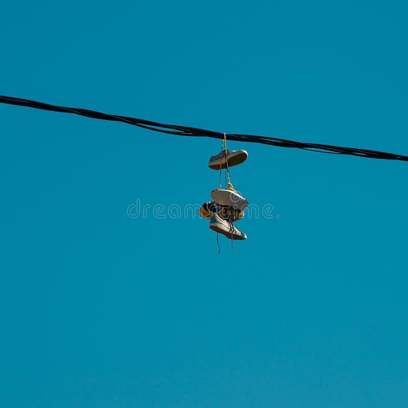 Turnschuhe, die an einem Himmelhintergrund hängen Das Konzept der städtischen Kultur, Verkauf von verbotenen Substanzen, Getto lizenzfreie stockfotos