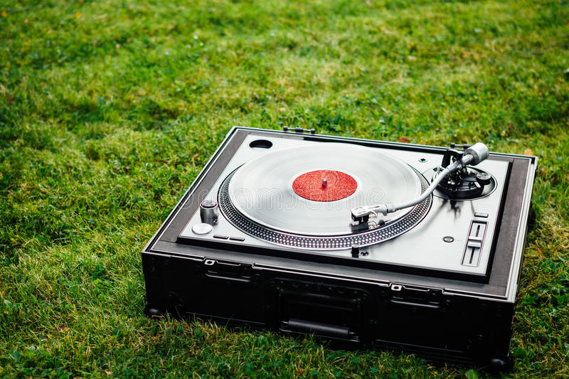 Turntable with LP vinyl record on grass background. Turntable with LP vinyl record on green grass background stock photography