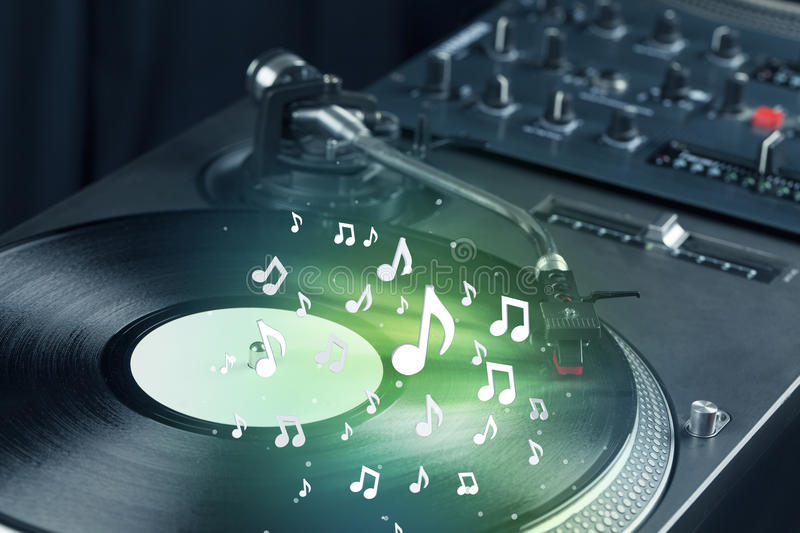 Turntable playing music with audio notes glowing. Concept on background stock image