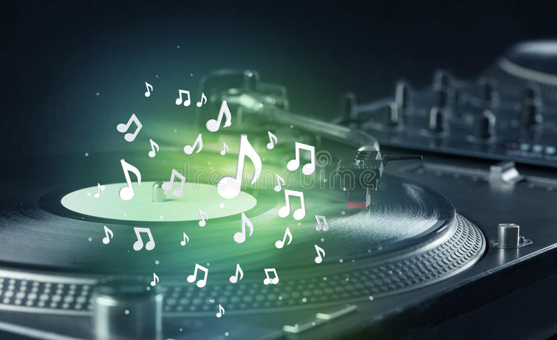 Turntable playing music with audio notes glowing. Concept on background stock photo