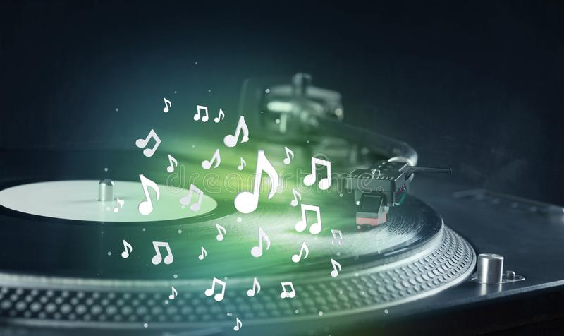 Turntable playing music with audio notes glowing royalty free stock photography