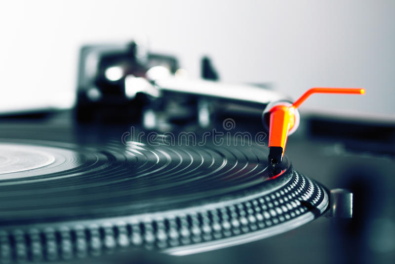Turntable playing vinyl record. Professional audio equipment for a DJ - turntable playing record with music royalty free stock photo
