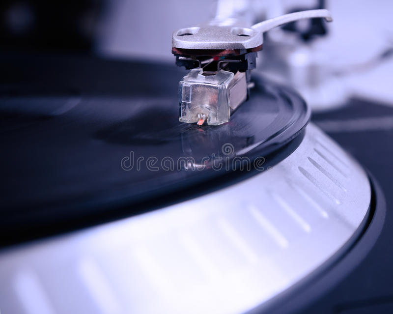 Turntable playing vinyl record with music. Close up, macro photo. Professional audio equipment for DJ, nightclub or audio enthusiast stock photo
