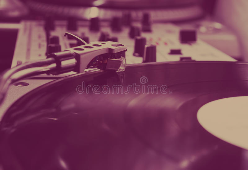 Turntable playing vinyl record with music. Close up, macro photo. Professional audio equipment for DJ, nightclub or audio enthusiast stock image