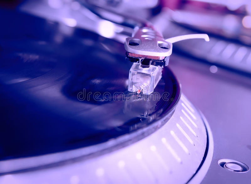 Turntable playing vinyl record with music. Close up, macro photo. Professional audio equipment for DJ, nightclub or audio enthusiast royalty free stock image