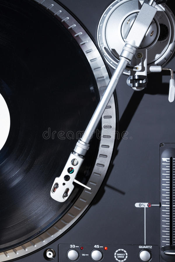 Turntable playing vinyl record with music. Professional sound equipment for a disc jockey. Turntable vinyl record players and 2 channel sound mixing controller stock photos