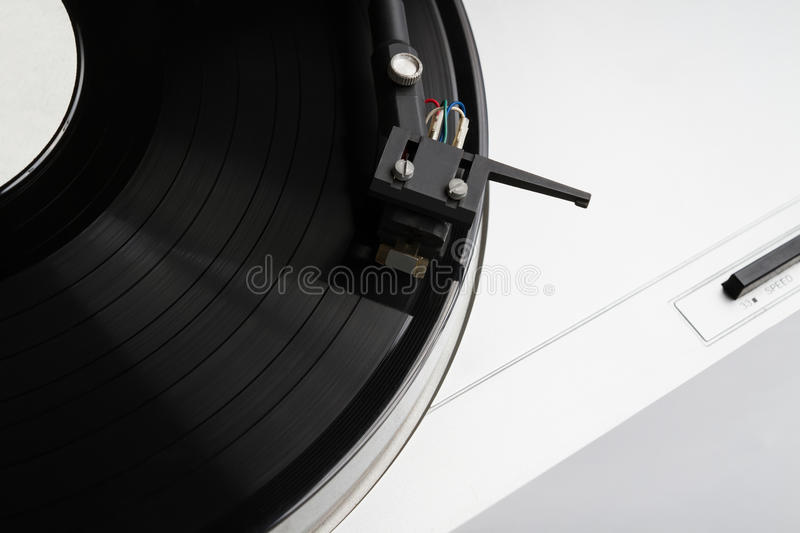 Turntable playing vinyl record with music. Useful equipment for DJ, nightclub and retro hipster theme or audio enthusiast stock photos