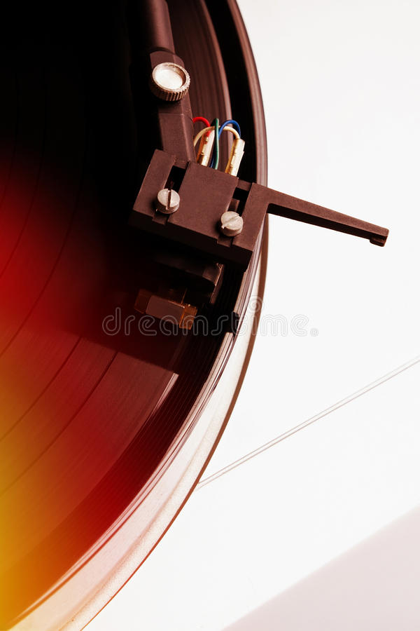 Turntable playing vinyl record with music. Useful equipment for DJ, nightclub and retro hipster theme or audio enthusiast. Light leak film filter effect stock image
