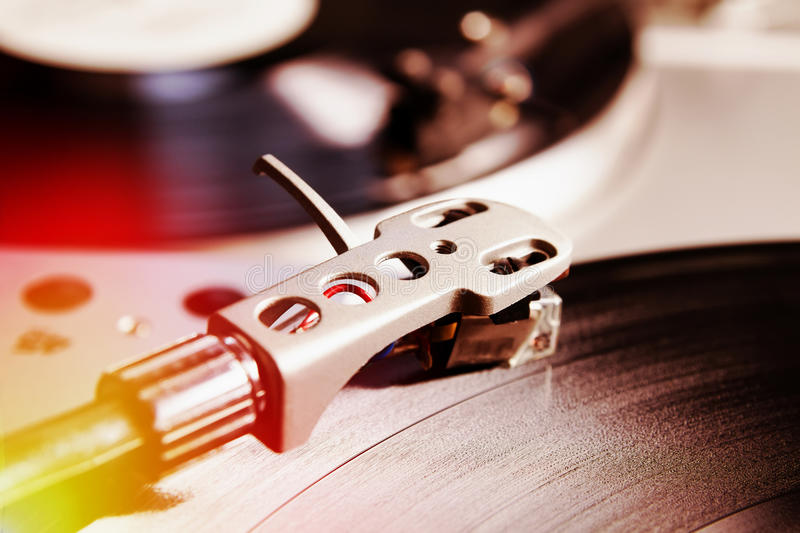 Turntable playing vinyl record with music. Useful equipment for DJ, nightclub and retro hipster theme or audio enthusiast. Light leak film hipster instagram stock photography